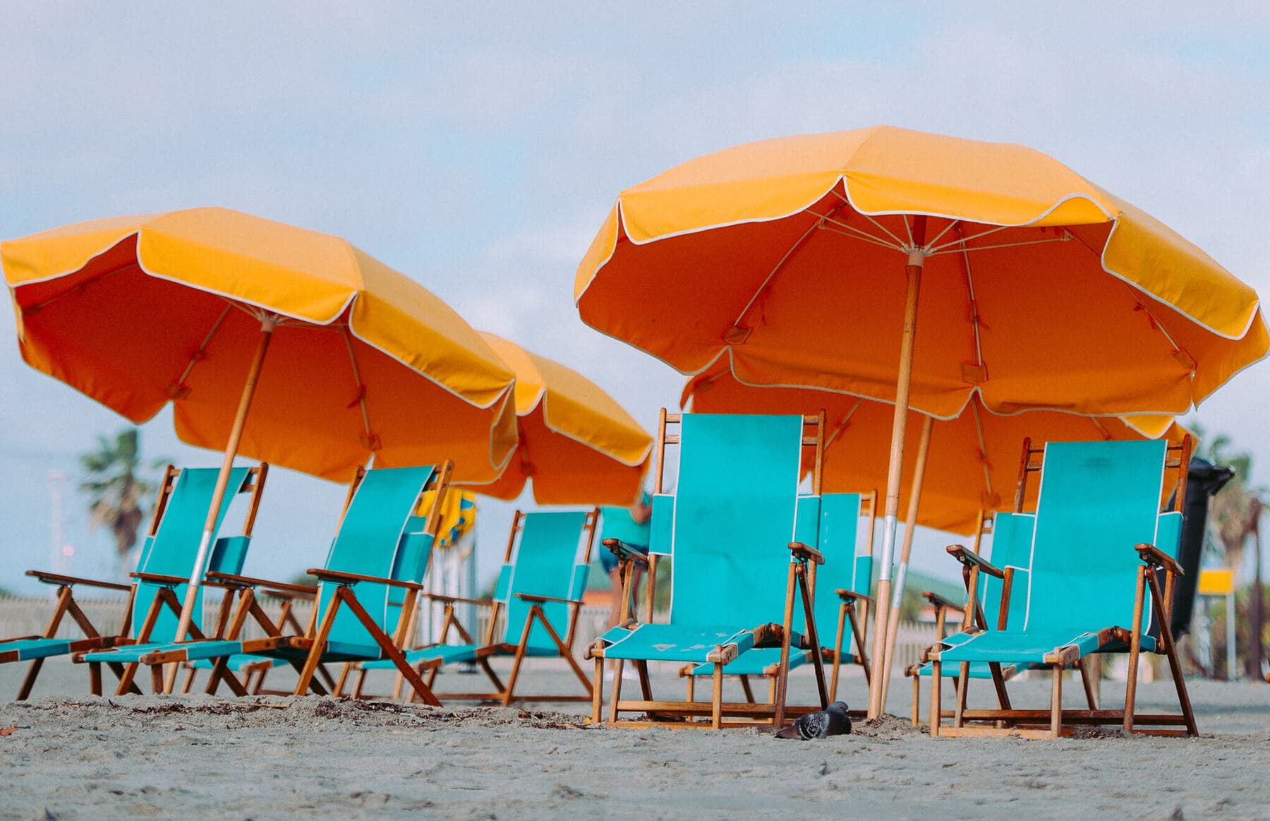 Green Beach Chairs on the Sand with Orange Umbrellas