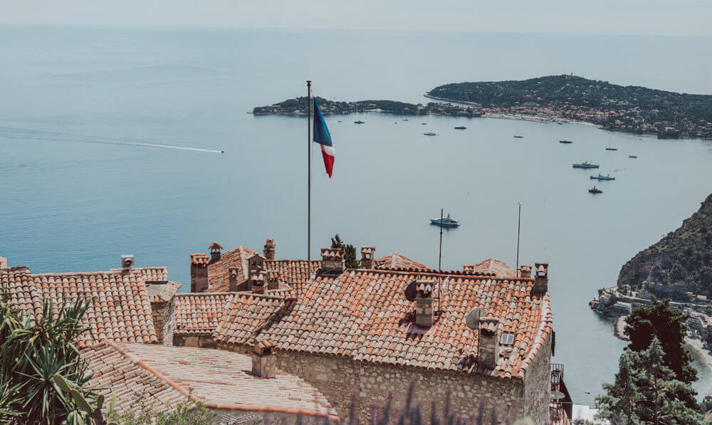French Flag on Orange Roof Over Coastline
