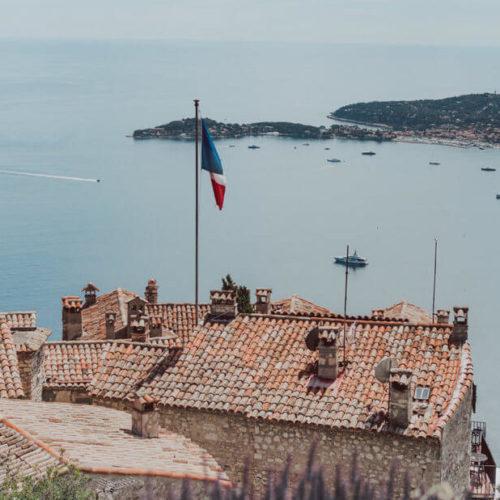 French Flag on Orange Roof Over Coastline