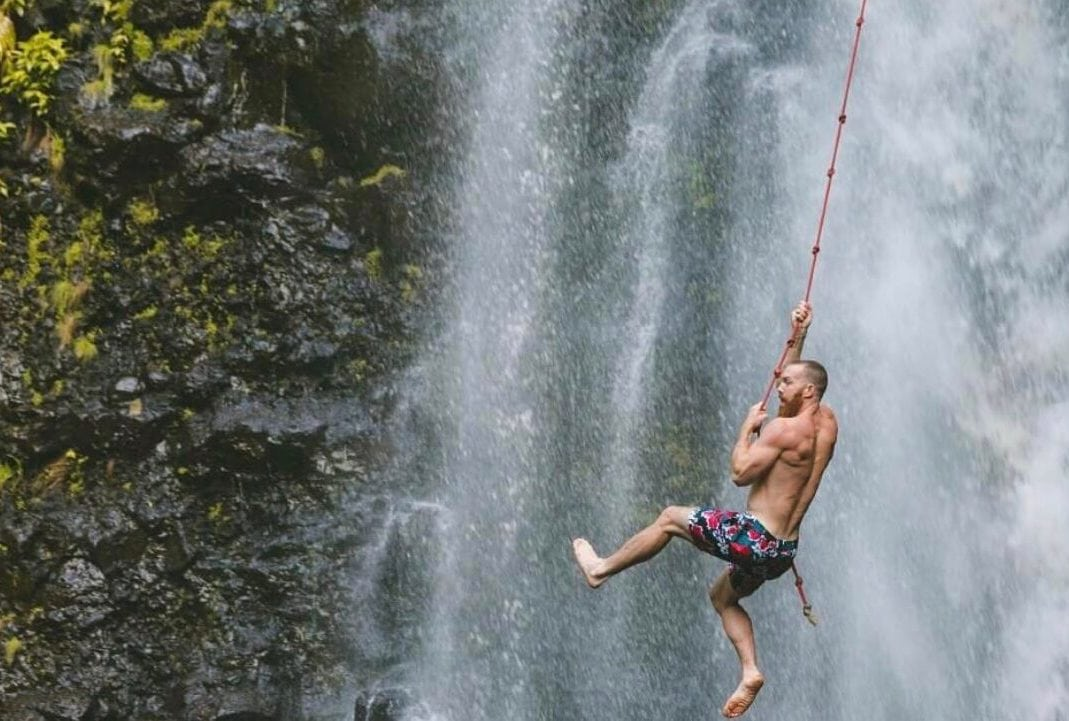 Man Swinging on Red Rope by Waterfall