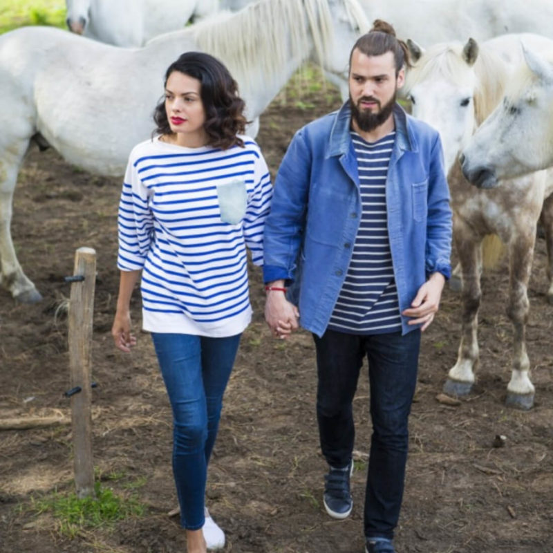 Men wearing La Marinière Française Victor Men's Blue Striped Tee OuiPlease Homme Men's Shop and women holding his hand horses in background