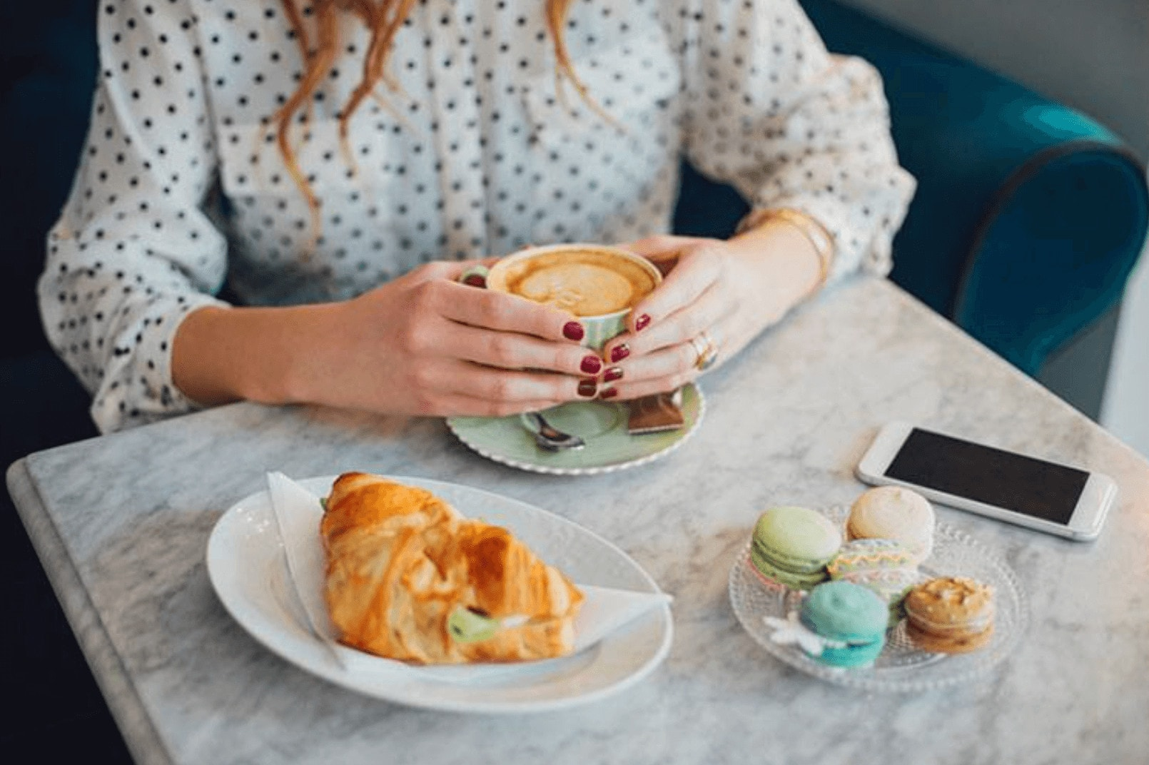 WOMAN DRINKING COFFEE, FRENCH MACARONS, CROISSANT