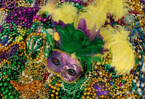 Purple mardi gras mask with yellow feathers