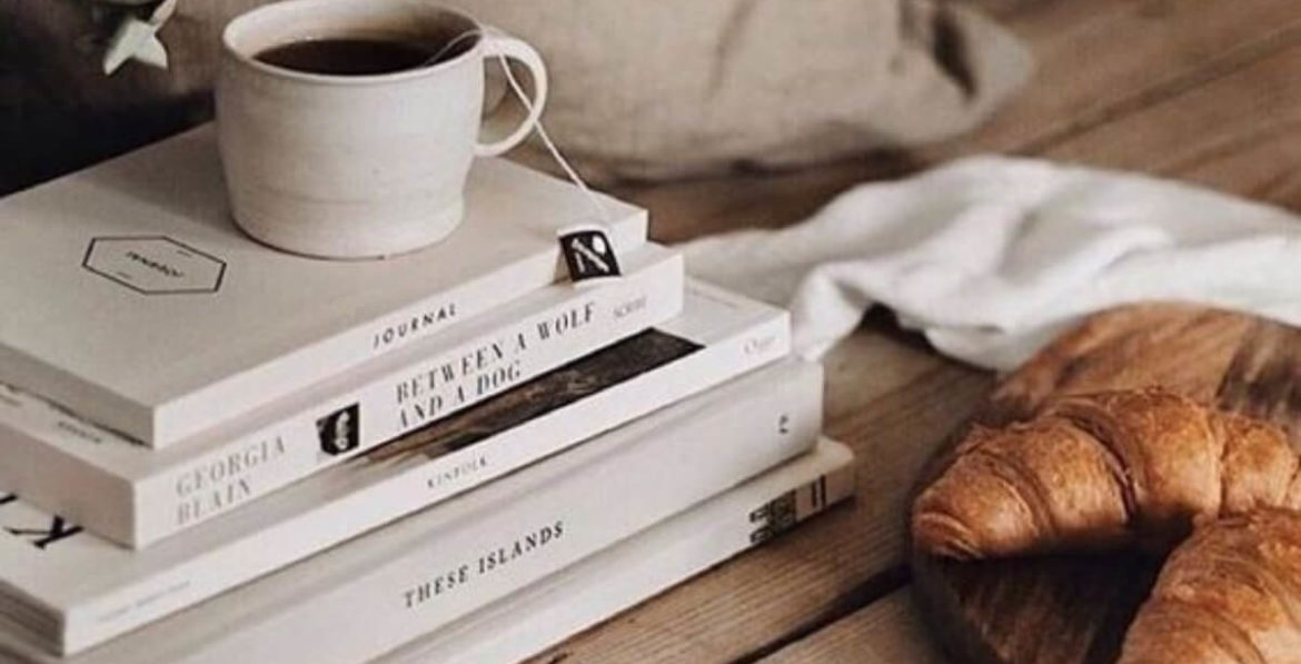 stacked books with coffee and a croissant