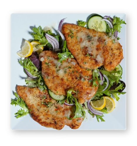 Chicken Paillard with garnish & lemon wedges