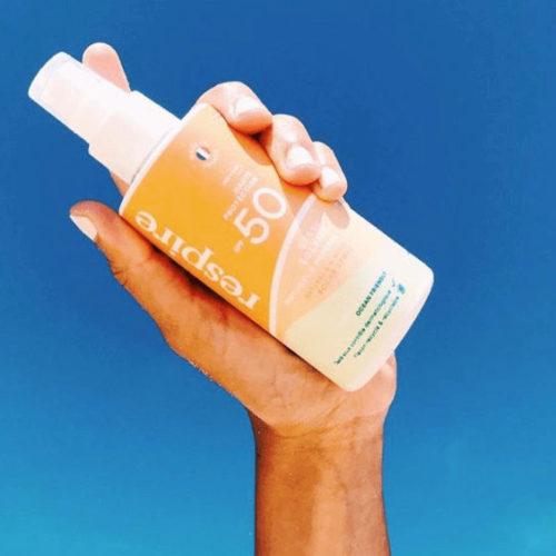 hand holding sunscreen bottle